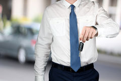 Young successful businessman offering a car key. Royalty Free Stock Image