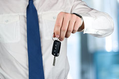 Young successful businessman offering a car key. Close-up of dri Stock Photos