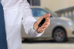 Young successful businessman offering a car key. Close-up of dri Royalty Free Stock Photography