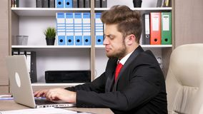 Young successful businessman in the office typing on the laptop. Dolly parallax type footage stock footage