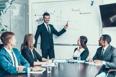 Young successful businessman points to board showing company development schedule. Royalty Free Stock Image