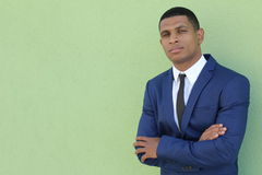 Young successful businessman posing in elegant suit against green background with copy space Royalty Free Stock Photos