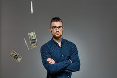 Young successful businessman posing among falling money over dark background. Stock Image