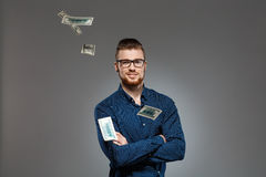 Young successful businessman posing among falling money over dark background. Stock Photography