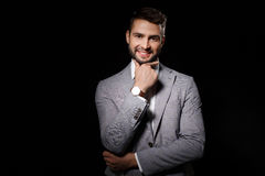 Young successful businessman posing smiling  isolated on black background. Royalty Free Stock Photo