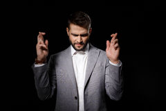 Young successful businessman praying with crossed fingers on black background. Stock Photos