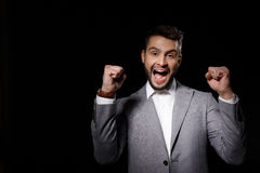 Young successful businessman rejoicing isolated on black background. Copy space. Royalty Free Stock Photos