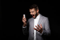Young successful businessman shouting looking at phone over black background. Royalty Free Stock Photo