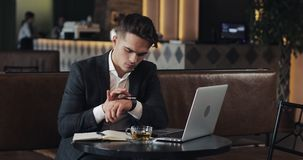 Young successful businessman with smartwatch sitting in cafe. Freelancer view the messages, activate the applications stock video