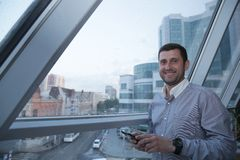 Young successful businessman with a smile on his face looks at the news on a mobile phone on the background of a panoramic window. On a high floor, overlooking royalty free stock photo