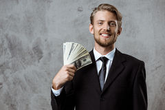 Young successful businessman smiling, holding money over grey background. Royalty Free Stock Images