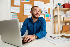 Young successful businessman smiling, sitting at workplace with laptop. Office background. Royalty Free Stock Photography