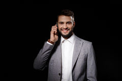 Young successful businessman smiling speaking on phone over black background. Royalty Free Stock Photo