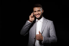 Young successful businessman smiling speaking on phone over black background. Stock Photo
