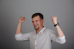 Young successful businessman standing with hands up and celebrating success. Royalty Free Stock Photo
