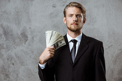 Young successful businessman in suit holding money over grey background. Royalty Free Stock Photography