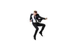 Young successful businessman in suit rejoicing, jumping over white background. Stock Image