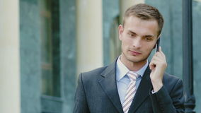 Young successful businessman talking on the phone outdoors. Young successful businessman talking on the phone stock footage