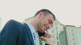 Young successful businessman talking on the phone outdoors. He looks very happy conversation stock footage