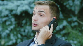 Young successful businessman talking on the phone outdoors. He sits on the bench and looks very happy conversation stock footage