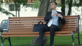 Young successful businessman talking on the phone outdoors. He sits down on the bench takes documents from the portfolio and conducts business conversation stock video footage