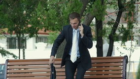 Young successful businessman talking on the phone outdoors. He sits down on the bench takes documents from the portfolio and conducts business conversation stock video