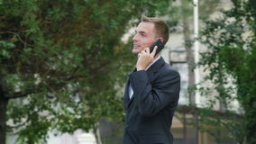 Young successful businessman talking on the phone outdoors. Young successful businessman talking on the phone. In slow motion stock video