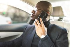 Young successful businessman talking on the phone sitting in the backseat of a expensive car. Negotiations and business royalty free stock photo