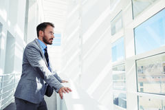Young successful businessman thinking about something while looking in big office building, Stock Image