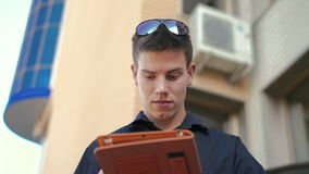 Young successful businessman using tablet outdoor near the office. In Full hD stock video footage