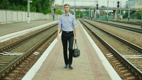 A young successful businessman walks along the railway station along the tracks. He carries a bag in his hand, smiles. A. Successful business trip. Steadicam stock video