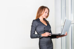 Young successful businesswoman with laptop computer standing near the window. Woman using tablet computer. Business Royalty Free Stock Photo