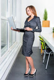 Young successful businesswoman with laptop computer standing near the window. Woman using tablet computer. Business Royalty Free Stock Photography