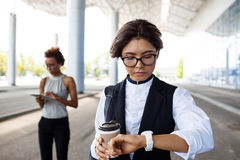 Young successful businesswoman looking at watch, standing near business centre. Royalty Free Stock Images