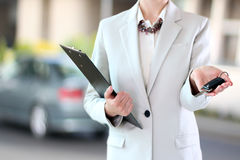 Young successful businesswoman offering a car key. Royalty Free Stock Images