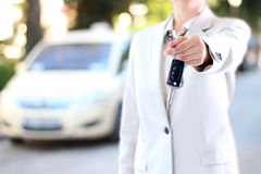 Young successful businesswoman offering a car key. stock photography