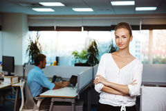 Young successful businesswoman smiling, posing with crossed arms, over office background. Royalty Free Stock Photography