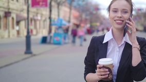 Young successful businesswoman using smart phone in city downtown, professional female employer talking with business. Partner drinking coffee. Business stock video footage