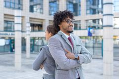 Young successful busness couple standing back to back royalty free stock photo