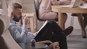Young successful Caucasian businessman reading through documents in an armchair, drinking coffee from mug in office. Modern manager enjoying working in stock footage