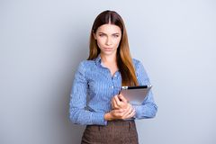 Young successful and confident  business lady is holding tablet. And looks in camera. She is wearing smart formal clothes and behind her is a pure background Royalty Free Stock Images