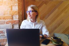 Young successful confident girl-Manager, freelancer, business lady with glasses works on a laptop computer in the interior of the stock image