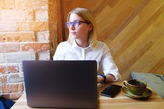 Young successful confident girl-Manager, freelancer, business lady with glasses works on a laptop computer in the interior of the stock images