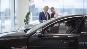 A young successful couple watching a confident girl sitting in the cabin of a new, expensive car on the driver`s seat at. A car showroom stock footage