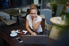 Young successful female freelancer using laptop computer for remote work while sitting in cafe bar, Stock Photo