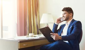 Young successful financier consulting client or partner by smarthone. Young successful financier with papers sitting in hotel room and consulting client or royalty free stock images