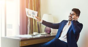 Young successful financier consulting client or partner by smarthone. Young successful financier with papers sitting in hotel room and talking on smarthone royalty free stock photo