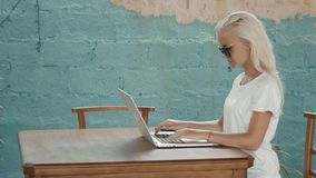 Young successful freelancer female enjoys while working on a portable computer during summer vacation. Blonde woman. Young successful freelancer female enjoys stock video footage