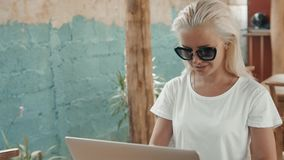 Young successful freelancer female enjoys while working on a portable computer during summer vacation. Blonde woman. Young successful freelancer female enjoys stock footage
