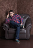 Young successful guy sitting on a leather armchair. Cool royalty free stock photography